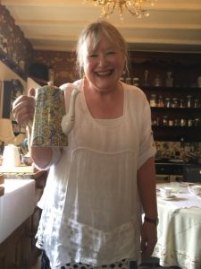 Sheila smiling at camera holding a tea pot at her coffee day